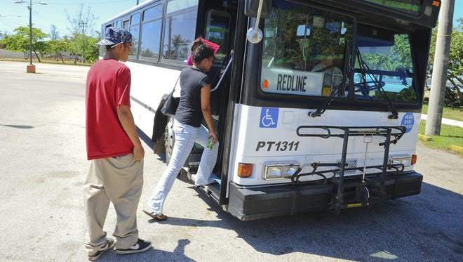 Passengers board the Guam Mass Transit Authority's Redline bus at a bus stop in the Paseo parking lot in Hagåtña in May 2013.