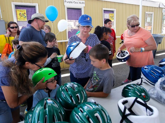 Volunteer Jo Duckwitz, center, helps children find a free bike helmet Saturday at KidFest at McGee Park.