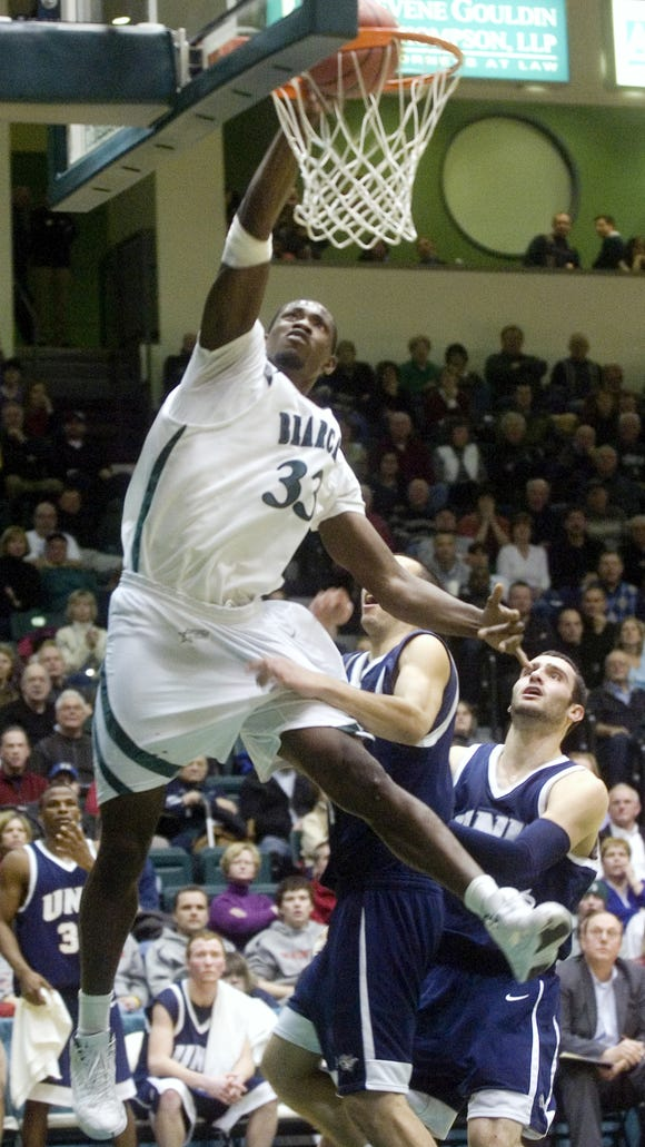 Former Binghamton University center Kyrie Sutton, left, dunks the ball past University of New Hampshire's Dane DiLiegro, right, and James Valladares during a game at the Events Center in 2010.