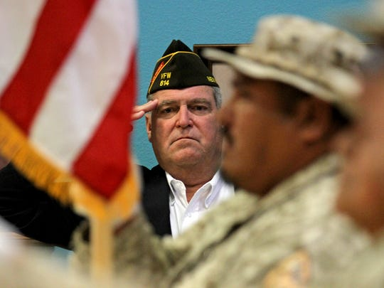 Jesse Coleman, post commander for VFW Post 614, stands for the Pledge of Alligence on Tuesday during a Vietnam medals award ceremony at the Bonnie Dallas Senior Center in Farmington.