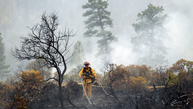 A firefighter with the Anderson, Calif., Fire Protection District dousing hot spots left behind by the Eiler Fire near Burney, Calif.