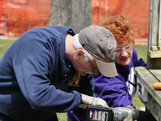 Dave Whipple and Denise Brooks demolish a porch at