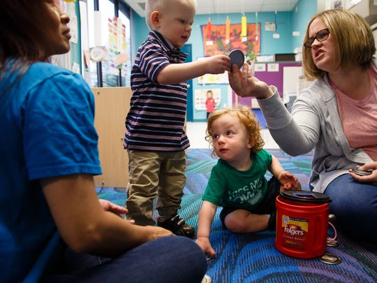 Teachers Allison Vuong, left, and Carrie Moore, right, play a game with 1-year-olds Patrick Lawerence, center right, and Colton Lenherdt, center left, at the The Child Development Center at UnityPoint Health on Friday, May 11, 2018, in Des Moines. The center has been providing childcare for UnityPoint employees for 52 years and has been a major factor in attracting and keeping quality employees said Sue Huffman, Director of the Child Development Center.