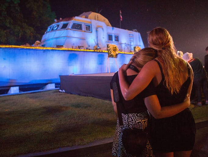 Two tourists comfort each other during a memorial service