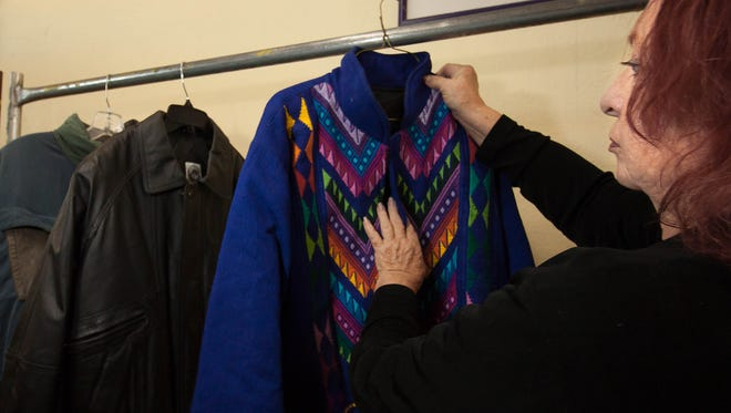 The Gospel Rescue Mission's Clothing Room Manager Wylene Saunders hangs one of the last remaining coats after a busy day in November 2015. The mission is again asking for the community's help donating winter clothes and blankets.