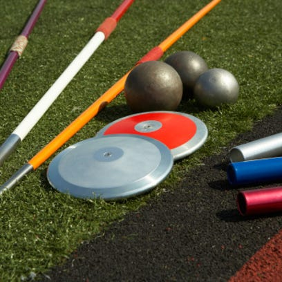 Javelins, discuses, relay batons and shots beside track