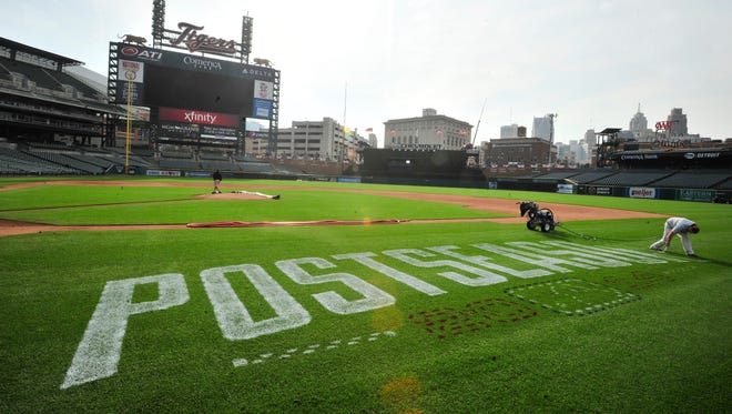 Tigers grounds crew works on painting the 'Postseason' logos for the 2014 playoffs at Comerica Park.