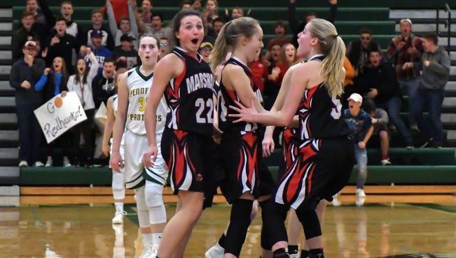 Marshall teammates react after Morgan Tatrow (13) hits a 3-pointer from half-court at the halftime buzzer Friday night.