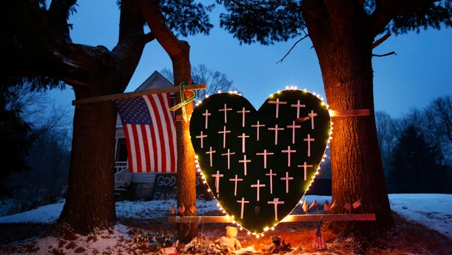 In this Dec. 14, 2013 file photo, a makeshift memorial with crosses for the victims of the Sandy Hook Elementary School shooting massacre stands outside a home in Newtown, Conn., on the one-year anniversary of the shootings.