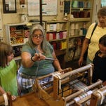 Ruth Bennett shows Darlene Miller (far right) and her two granddaughters, Leyla Miller (right) and Elizabeth Miller, how to weave a thread of yarn in a loom during a tour of the Tophouse cabin located on the Lou Tate Little Loomhouse grounds, Thursday, June 25, 2015.