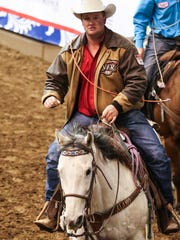 Sam Powers rides in the arena between events during