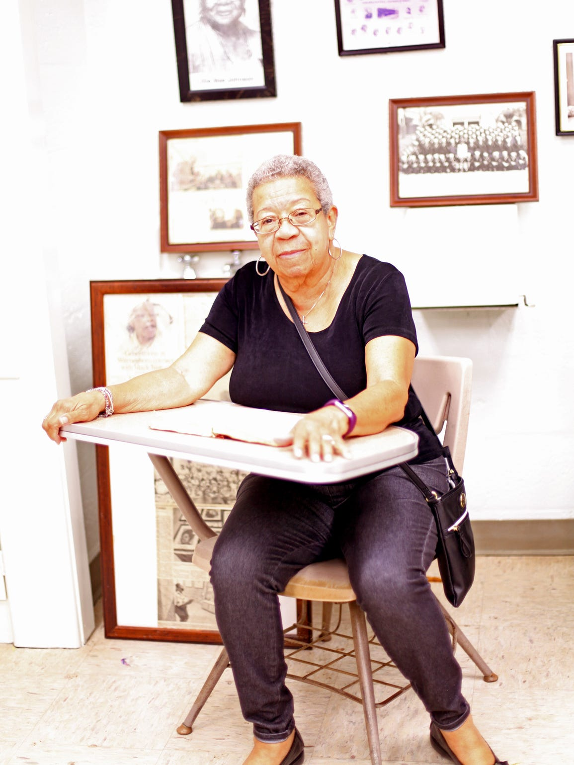 Charlotte Redd Wood sits in an old desk from Rosenwald