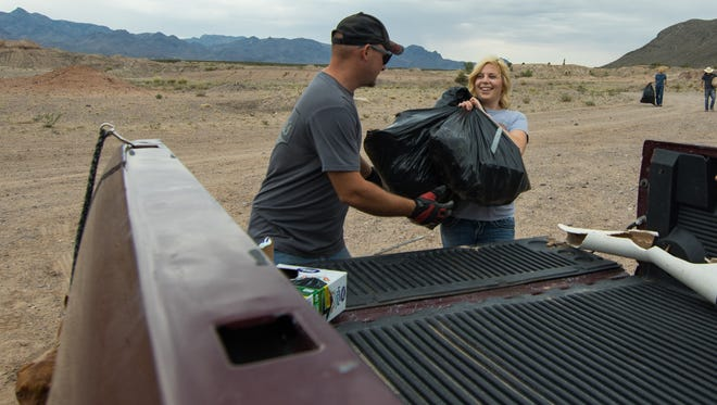 Collin Miesen and Kayla Smith pitch in to beautify the desert area near A-Mountain as part of the Offroad.NewMexi.co cleanup day on Saturday, June 11, 2016.