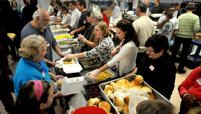 Volunteers serve food at the annual Eileen Hickey Thanksgiving Dinner in 2013 at the Lunch Box in the City of Poughkeepsie.