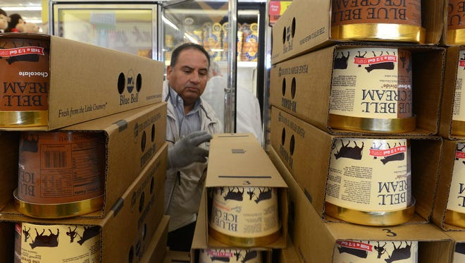 Robert Maldonado with Blue Bell Ice Cream out of El Paso, Texas, restocks containers of the ice cream Monday morning, Dec. 14, 2015 at the Albertsons Market on Eighth Street in Odessa, Texas. Seven Blue Bell flavors returned to grocery shelves in Odessa, across Texas and Alabama Monday after Blue Bell recalled of all its products in April traced to listeria contamination.