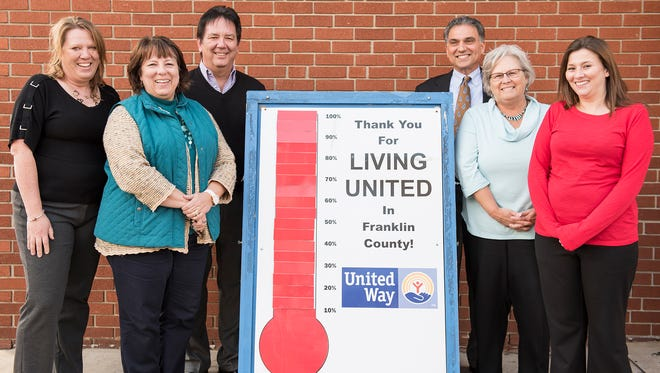 United Way of Franklin County's staff stand outside with a sign showing that they succeeded in raising their goal of $750,000 in Chambersburg, Pa. on Wednesday, March 2, 2016. United Way of Franklin County in total raised $752,030 from Sept. of 2015 till Feb. 29, 2016.