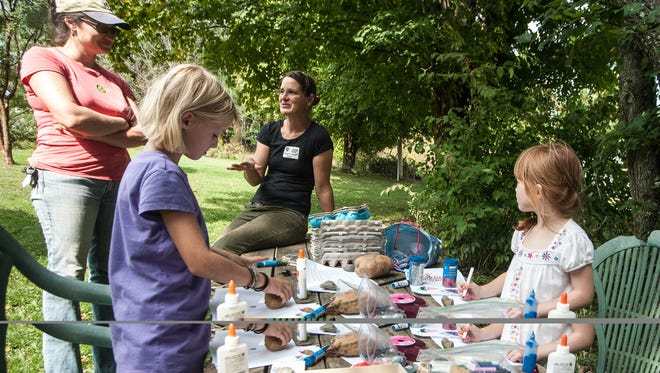 Belle Campbell and Megan Hearne(right) play at the kids table while their mothers Vanessa Campbell and Julianna Hearne (left) discuss growing vegetables at Full Sun Farm during ASAP's 2014 farm tour.