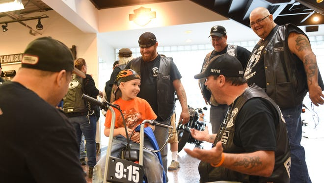 "Lucas Steigelman, 7, of Lebanon, tells ""Defaut"" (kneeling) he can't ride his minibike as Lucas sits on it after the 2nd Amendment Lebanon County chapter of the Iron Order Motorcycle Club presented the minibike to him on Thursday, Sept. 22, 2016, at Iron Valley Harley-Davidson. Steigelman was diagnosed with leukemia in January. The club will hold a poker run Saturday, beginning at 11:30 a.m.  at Moose's LZ Bar & Grill, 211 Fisher Ave., Jonestown, to benefit Steigelman."