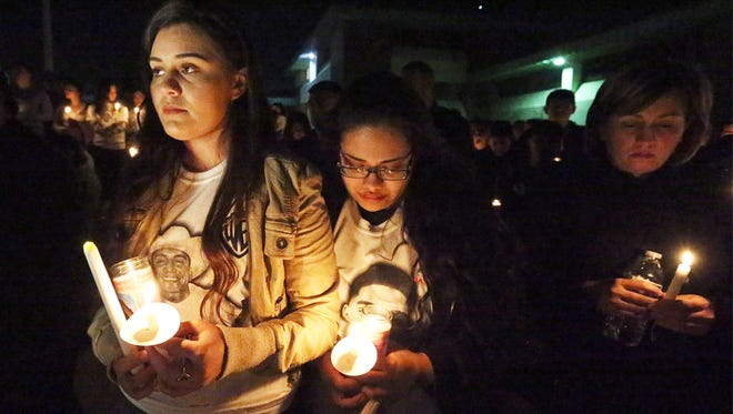 "Yesenia Franco, left, and friend Jasmin Sida take part in a candlelight vigil for Franco's cousin, Rogelio ""RJ"" Franco Jr. Wednesday night at Montwood High School. About 300 people attended. Rogelio ""RJ"" Franco was killed in the parking lot of an East side bar Sunday night. He was a 2013 graduate of the East side school."