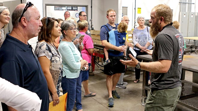 Teacher Rusty Brixey (right) talks with a group touring the Wichita Falls ISD's new Career Education Center about the agricultural welding lab and program during an open house on Sept. 14.