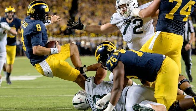 Michigan State's Kenney Willekes, bottom, sacks Michigan's John O'Korn during the second quarter on Saturday, Oct. 7, 2017, at Michigan Stadium in Ann Arbor.