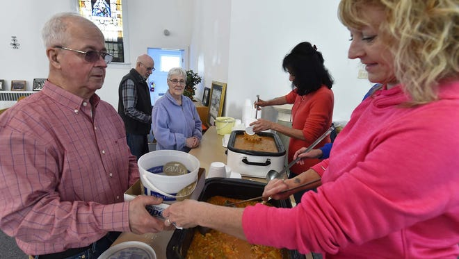 Amy Stanelle of Sturgeon Bay ladles up a bowl of booyah for Cletus LeCaptain of Rosiere during last year's Booyah and Bread event at the Belgian Heritage Center.