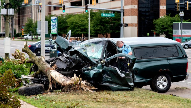 A Lansing Police officer works the scene of a crash involving at least two vehicles on Pennsylvania Avenue south of Michigan Avenue on Friday, June 22, 2018, in Lansing. A truck involved in the accident knocked over a tree between the road and sidewalk. Police blocked Pennsylvania Avenue from south of Michigan Avenue to Eureka Street during the investigation.