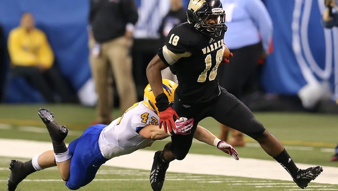 Warren Central's Mykelti Williams tries to shake a tackle from Carmel defender Jack Conway in the first half of the IHSAA Class 6A State Football Finals held at Lucas Oil Stadium on Saturday, November 30, 2013.