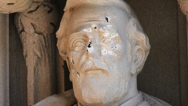 A defaced statue of Gen. Robert E. Lee statue stands at the Duke Chapel on Thursday, Aug. 17, 2017, in Durham, N.C.  Duke University removed the statue early Saturday, Aug. 19, days after it was vandalized amid a national debate about monuments to the Confederacy.