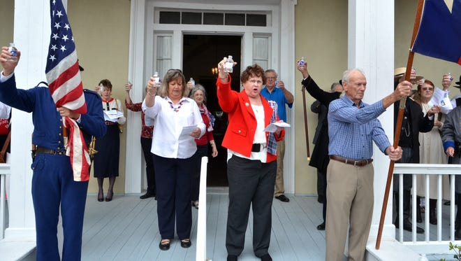 """Anita Eisenhauer (in red), Chairman, Nueces County Historical Commission, and Theresa Bluntzer Baucum (center left in white), President of the Clara Driscoll Chapter of the Daughters of the Republic of Texas, lead a """"Toast to Texas"""" during the Texas Independence Day celebration in front of the Centennial House on Upper Broadway, Sunday afternoon, hosted by Clara Driscoll Chapter of the Daughters of the Republic of Texas and the Nueces County Historical Society."""