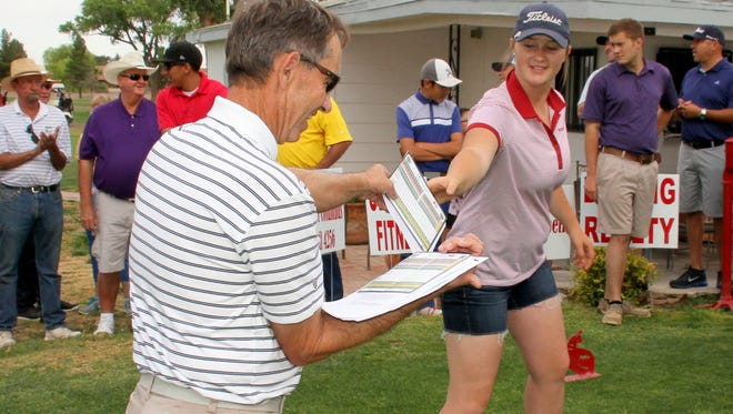Rio Mimbres Golf Pro James Williams hands a scorecard  to Lady Wildcat golfer Presley Jackson. Rio Mimbres Golf Course hosted the largest turnout to-date for the Steve Bean Memorial Golf Tournament on Saturday. The tournament draws players from local and area businesses, as well as the golfing community to raise money in memory of Steve Bean, a certified Emergency Medical Technician who was the first to train firefighters and first responders locally and also was instrumental in bring the hospital and Deming Fire Department into a positive working relationship. Money raised from the tournament is put into a scholarship fund by the Community Healthcare Foundation to serve a local student pursuing a career in the medical field.