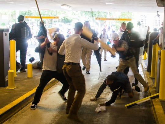 This photo of several men attacking 20-year-old Deandre Harris was taken Saturday afternoon in a parking garage in Charlottesville, Virginia, right next to the police department. A former Mason High School student has been accused on social media of being the attacker wearing the white construction hat.