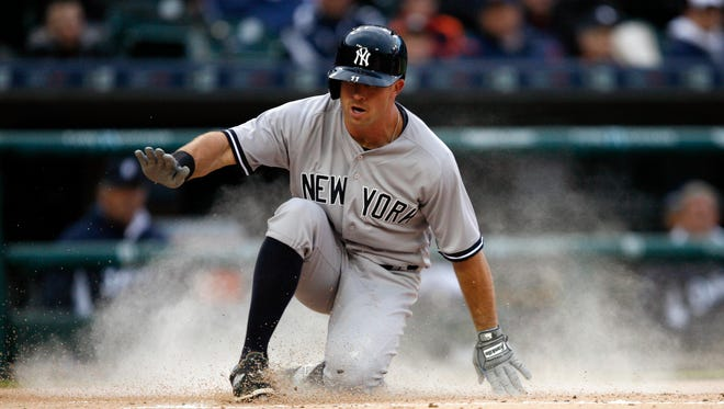 New York Yankees left fielder Brett Gardner (11) slides into home uncontested and scores a run during the first inning against the Detroit Tigers at Comerica Park.
