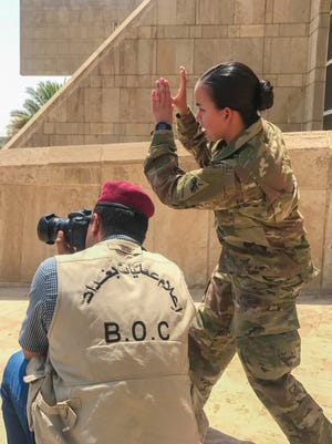 Sgt. Von Marie Donato, a public affairs NCO with 1st Armored Division, provides media and photography training to an Iraqi security forces member in Baghdad. The 1st Armored Division headquarters is in Iraq and leads the Combined Joint Forces Land Component Command.