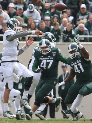 Michigan State quarterback Connor Cook jumps to throw over the defense during the Michigan State spring football game at Spartan Stadium on April 25, 2015. The White team beat the Green team 9-3.