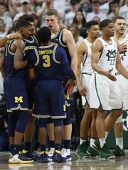 Michigan players huddle after a basket against Michigan
