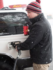 Colton Nelson puts gas in his SUV on a snowy Tuesday, March 20, 2018 at Rutter's, South Main Street, Chambersburg. A spring snowstom brought a few inches of snow to the area, but more is expected overnight and Wednesday.