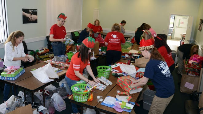 Volunteers and Florida Today employees wrap packages for seniors at Aging Matters in Brevard offices in Cocoa earlier this month.