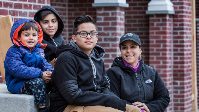 Five-year-old Xavier, 12-year-old Cristhian, and 14-year-old Jose Otero sit with their mother Aileen on the steps of their soon-to-be home in Wilmington on Thursday evening.