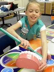 Fernley Elementary School fourth-grader Myleigh Mickelson uses an oversize toothbrush to practice brushing.