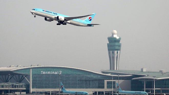 A passenger plane flies over Incheon International Airport on Jan. 18, 2018.