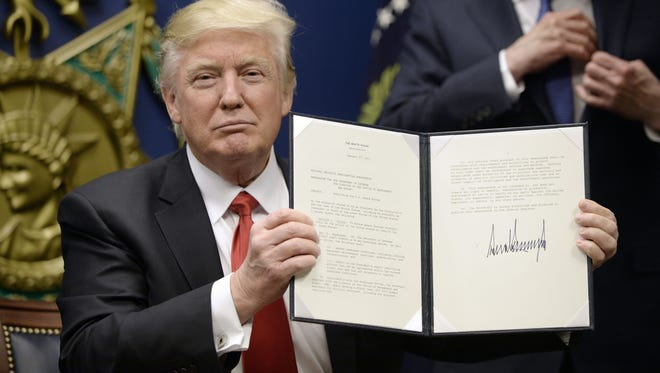 President Donald Trump signs executive orders in the Hall of Heroes at the Department of Defense on Jan. 27, 2017, in Arlington, Virginia.