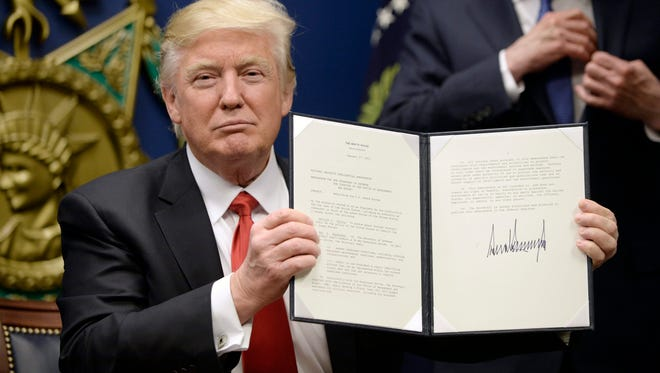 President Trump signs executive orders, including a temporary travel ban against people from seven majority-Muslim countries, at the Pentagon in Arlington, Va., on Jan. 27, 2017.