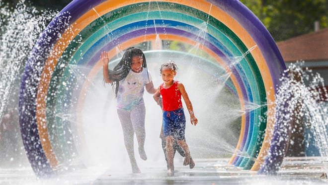 Neighborhood kids cool down from the heat by playing in the water at the Wes Montgomery Splash Park in Indianapolis on June 18, 2018.