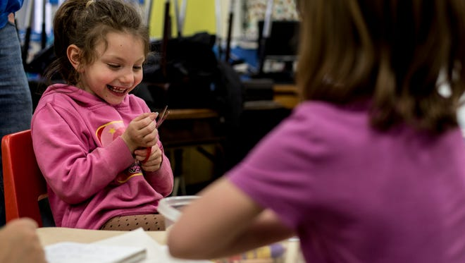 Aylea Sanchez, 6, laughs as she works on an activity with her tutor Joe Hurley, of Port Huron, during the Read for Life after-school program Wednesday, Feb. 1, 2017 at Woodrow Wilson Elementary School in Port Huron.
