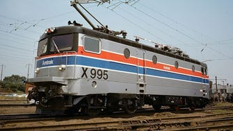 "In 1976, Amtrak tested French and Swedish locomotives on the Northeast Corridor in an attempt to find a replacement for the aging GG-1s. The Swedish model, an Rc4 locomotive designed by Allmanna Svenska Elektriska Aktiebolaget (ASEA), was designated the ""X995"" during its testing phase. Here it wears the Amtrak Phase II paint scheme introduced in 1975. The Rc4's lightweight design won out and became the basis for the Amtrak dual cab AEM-7. Amtrak contracted with the General Motors Electro-Motive Division to manufacture the AEM-7, which was produced  from 1978 to 1988 and could reach top speeds of 125 mph."
