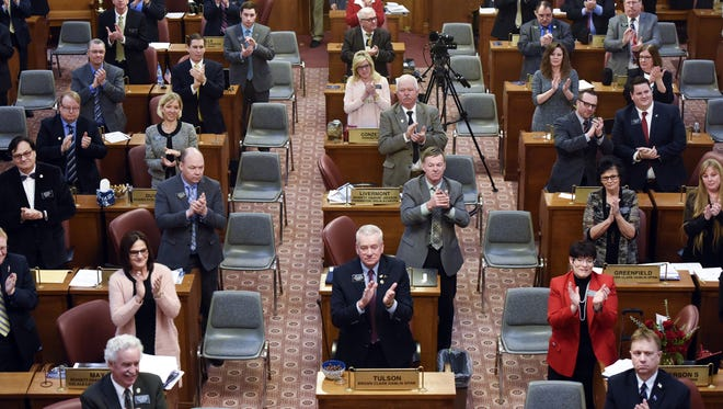 Representatives applaud at their desk sits in the South Dakota House of Representatives on Jan. 9, 2018 in Pierre, S.D.