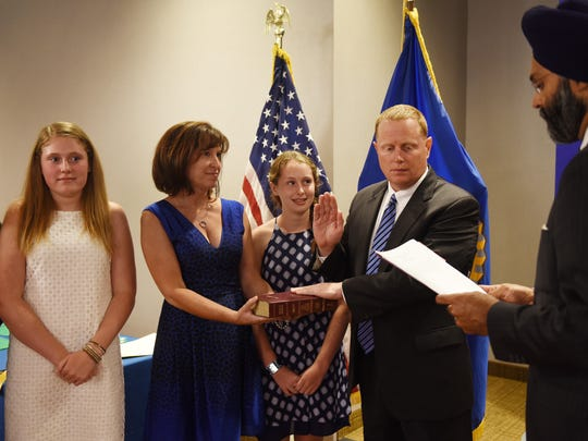Timothy Condon is sworn is as Deputy Chief of Detectives by Prosecutor Gurbir S. Grewal , as his family (L to R) Courtney (15), Donna (wife) and Caroline (14) look on during the Bergen County Prosecutors' Swearing-in Ceremony at Two Bergen County Plaza Conference Center in Hackensack on July 17th, 2017.