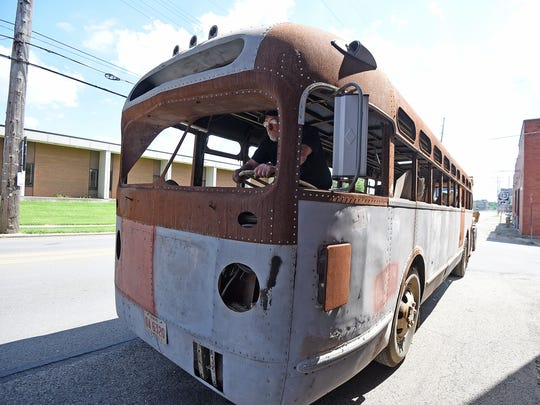 Hans Niederhauser steers a 1947 GM bus as it is pushed Monday morning on Fifth Street in Mansfield.