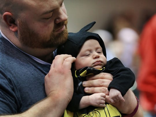 Eight-month-old Bruce Wayne Facsko of Noblesville, gets his costume adjusted by his dad Drew Facsko.